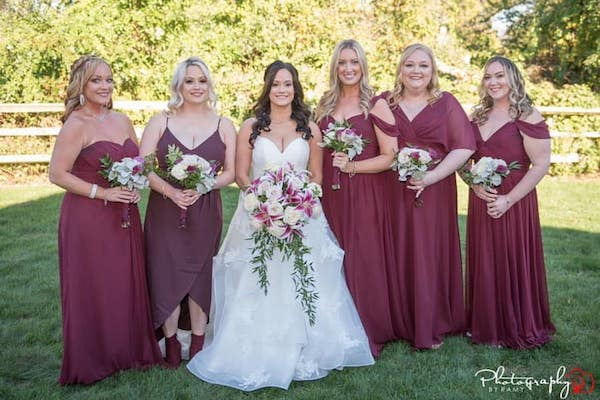 bride with her bridal party in burgundy dresses with burgundy and  white bouquets