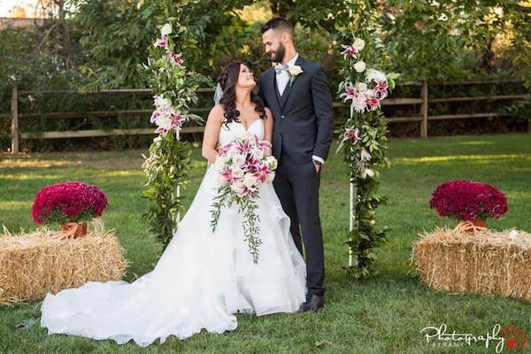 bride and groom under a wedding arch covered with burgundy and white flowers