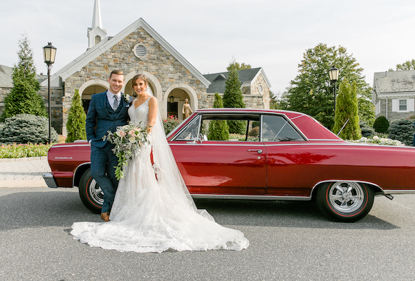 bride and groom posing for photos in front of a classic red Chevelle