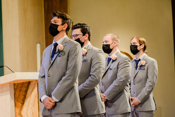 groomsmen with pale pink rose boutonnieres wearing protective face masks
