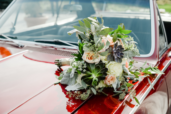 textured bridal bouquet with succulents and pink and white flowers sitting on a classic red Chevelle