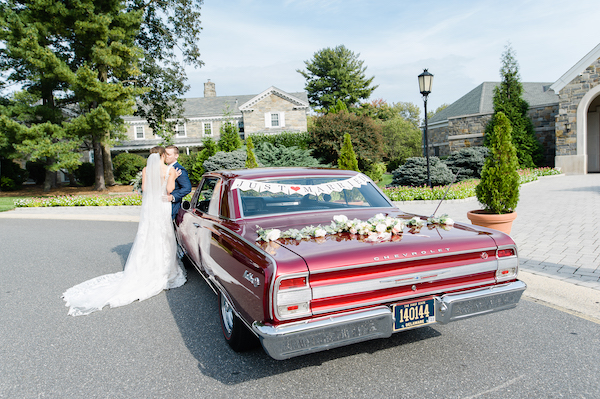 couple posing for photos in front of their classic red Chevelle with floral garland and Just Married sign