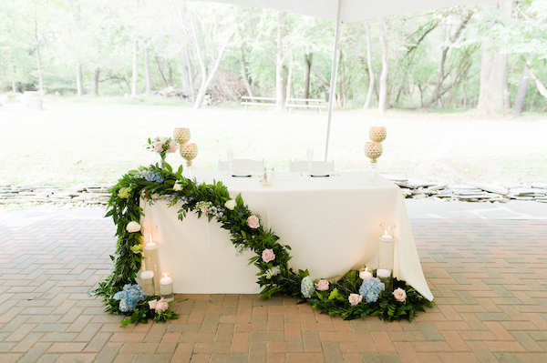 sweetheart table with floral garland and floating candles