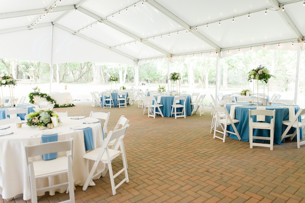 physically distant outdoor wedding under a tent with blue and white linens