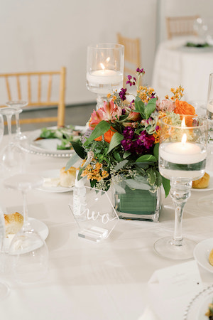 modern glass wedding tablescape with purple and orange flowers