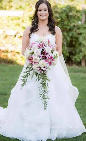 bride carrying a bouquet of white roses and stargazer lilies